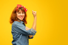 Smiling Middle Aged Woman With A Clenched Fist Rolling Up Her Sleeve On Yellow Background, Copy Space, Tribute To The Icon Rosie Riveter