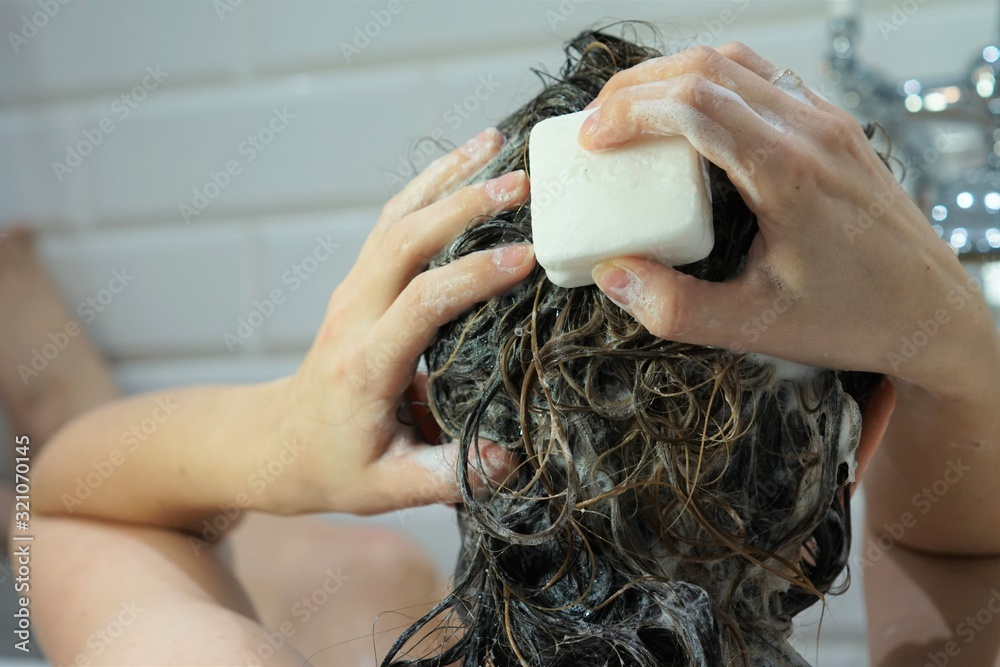 Fototapeta Caucasian woman washes her brown hair with shampoo bar or soap, zero waste concept