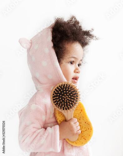 Cute little girl in soft bathrobe with hairbrush and loofah Canvas-taulu