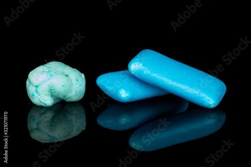 Group of two whole blue chewing gum with one bolus isolated on black glass Wallpaper Mural
