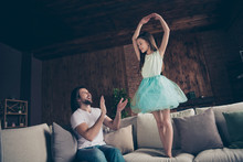 Photo Of Little Energetic Pretty Lady Excited Handsome Daddy Watching Daughter School Dance Raise Hands Like Ballerina Sitting Sofa Clapping Arms Ovation House Room Indoors