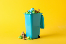 Recycle Bin With Trash On Yellow Background, Space For Text