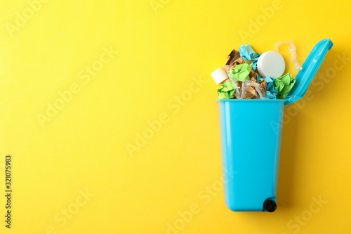 Photo Recycle bin with trash on yellow background, space for text