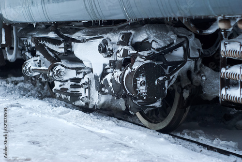 ice covered bogie of a railway passenger carriage on rails in winter Canvas Print