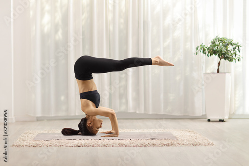 Young woman exercising a headstand pose Canvas-taulu