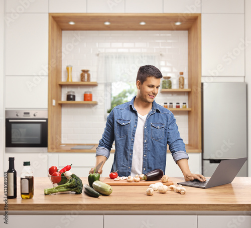 Fototapeta Young man cooking in a kitchen with a laptop obraz