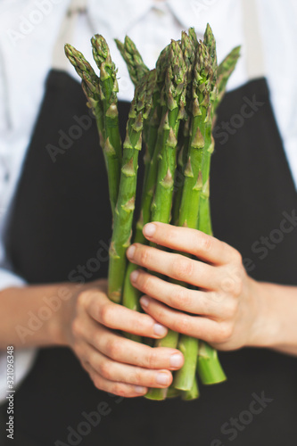 Photo woman holding a green asparagus in her hands