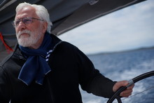 White Bearded Sailing Senior, Experienced Skipper On A Sailboat Holding The Steering Wheel While Looking To The Sea