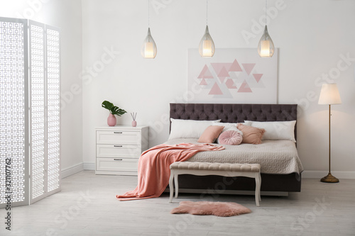 Fototapeta Stylish room interior with large comfortable bed obraz