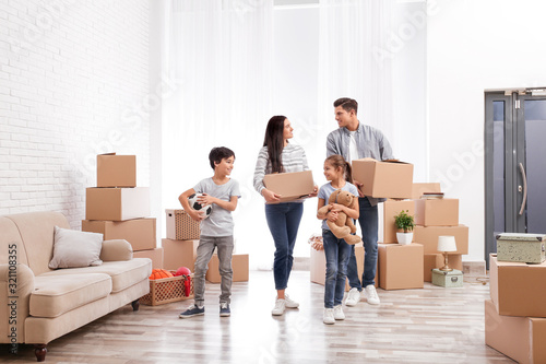 Happy family in room with cardboard boxes on moving day Wallpaper Mural
