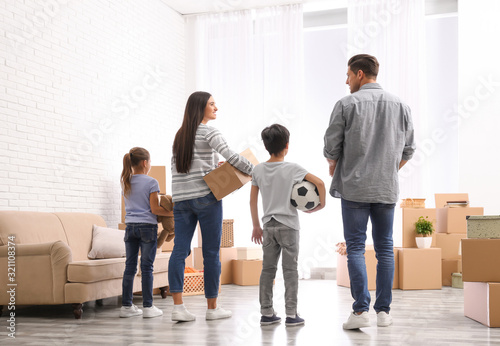 Family in room with cardboard boxes on moving day Canvas Print