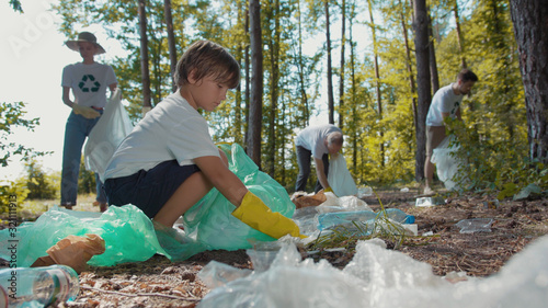 Volunteers activists people in gloves tidying up rubbish in park or forest envir Wallpaper Mural