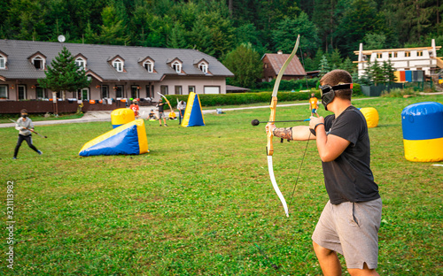 Teenage boy playing archery tag during summer Fototapete