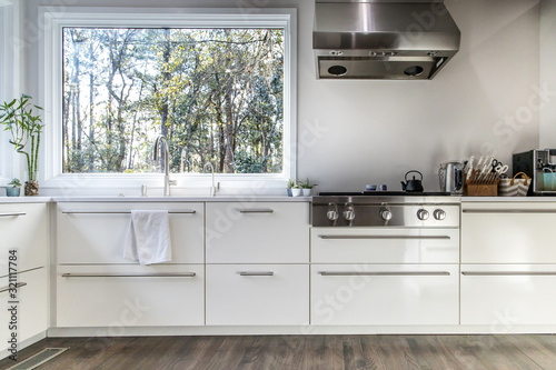 Fototapeta spacious large modern white kitchen recently updated with high end appliannces, wood floors, picture windows, white cabinets and wood beams and a great view of the backyard obraz