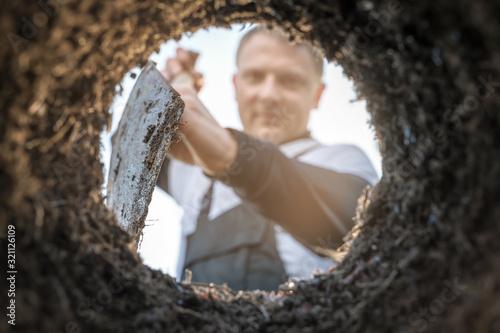 Fototapeta Gärtner gräbt mit einem Spaten ein Loch zum Anpflanzen von Pflanzen