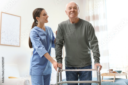 Photo Care worker helping elderly man with walker in geriatric hospice