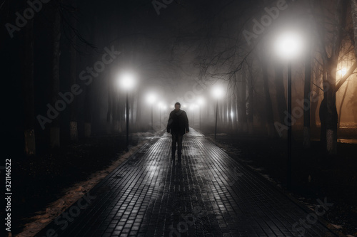 Fototapeta Sad man alone walking along the alley in night foggy park. Back view obraz