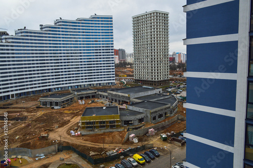 Fototapety, obrazy: Construction of a large multi-storey comfortable concrete cement modern new monolithic-frame multi-storey building with windows, walls and balconies