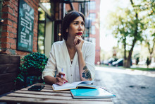 Thoughtful Female Schooler Sitting At Outdoors Table In Coffee Shop And Pondering On Information For University Essay, Intelligent Hipster Girl Thinking On Ideas During Memo Planning For Organisation