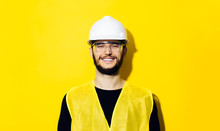Portrait Of Young Smiling Man, Builder Engineer, Wearing White Construction Safety Helmet, Glasses And Yellow Jacket Isolated On Yellow Background.