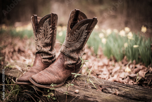 Fototapeta Worn western style cowboy boots out on old fence post obraz