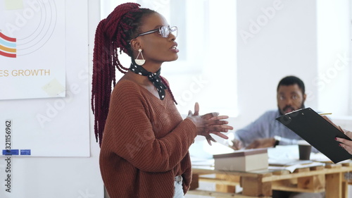 Happy young casual African woman boss in eyeglasses leading discussion, chatting to colleagues at modern light office Fototapet