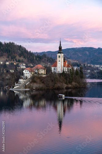 Island Church at Lake Blend in Slovenia during Sunrise. A Pletna boat is transporting tourists.