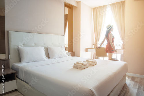 Fototapeta Tourist woman standing nearly window with her luggage in hotel bedroom. obraz