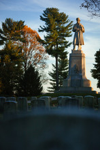 Private Soldier Monument At The Antietam National Cemetery In Sharpsburg, Maryland, USA With Headstoned In Foreground, Evening Light And Copy Space