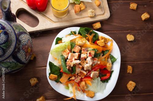 Ensalada Verde con pollo croutones y aderezo en mesa de madera Canvas Print