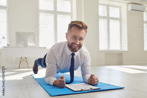 Businessman doing abs strap exercises while lying in the office. Tablou Canvas