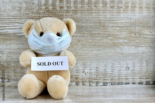 Announcement with text sold out held by a toy Teddy bear in a protective medical mask on a wooden background with respiratory masks Canvas Print