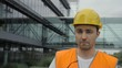 Construction worker talks to camera in front of modern building.