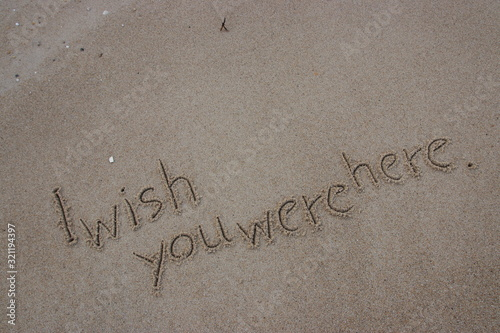 Photo Handwriting  words I wish you were here. on sand of beach.