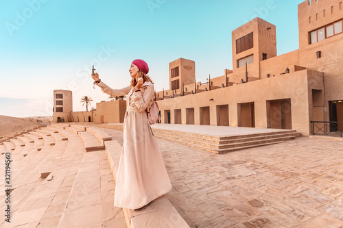 Happy woman traveler wearing dress and turban taking photos on her smartphone of an old Arab town or village in the middle of the desert Wallpaper Mural