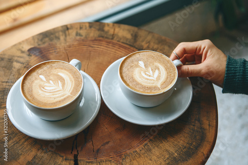 Two cups of aromatic coffee cappuccino or latte on a wooden table. person holds a cup with hand. Concept of meeting or relaxing. Tasty morning drinks. - 321200750
