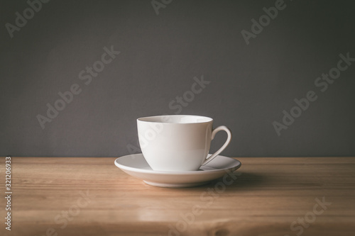 Fototapeta cup of coffee on wooden table with grey background obraz