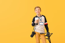 Little Journalist With Microphone And Camera On Color Background
