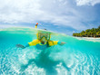 canvas print picture - Split underwater photo of child in mask snorkeling in blue ocean water near tropical island