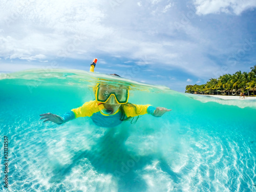 Split underwater photo of child in mask snorkeling in blue ocean water near trop Wallpaper Mural