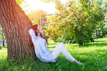 Young Woman Sitting Under Tree...