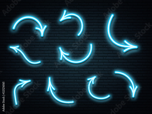 Photo Set of blue neon arrows glowing on dark brick wall background.