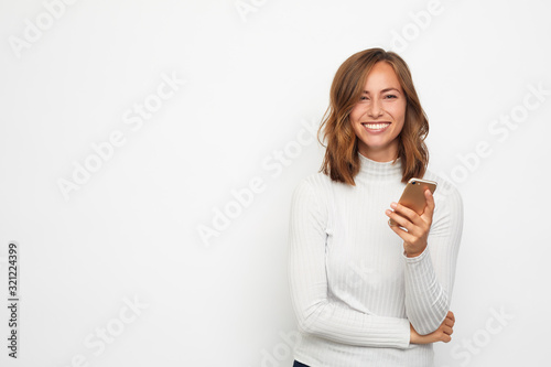 Obraz portrait of young beautyful woman on the phone looks in camera - fototapety do salonu