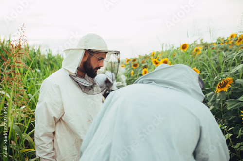 Two apiarist in the sunflowers field Canvas Print