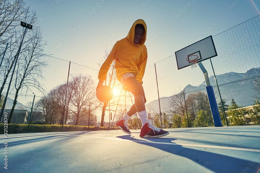 Fototapeta Athletic black man showing his backetball skills on court outdoors.