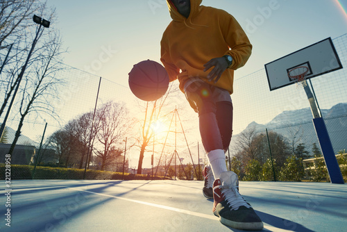 фотографія Athletic black man showing his backetball skills on court outdoors