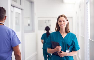 Portrait Of Smiling Female Doctor Wearing Scrubs In Busy Hospital Corridor Holding Digital Tablet