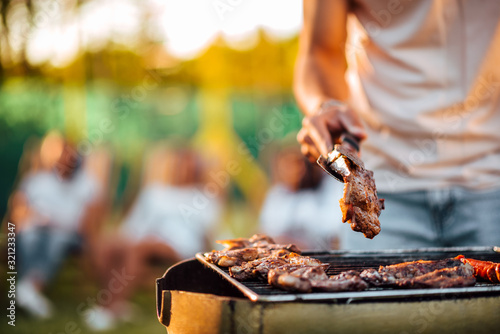 Fototapeta Close-up image of man barbecuing meat on the grill outdoors. obraz