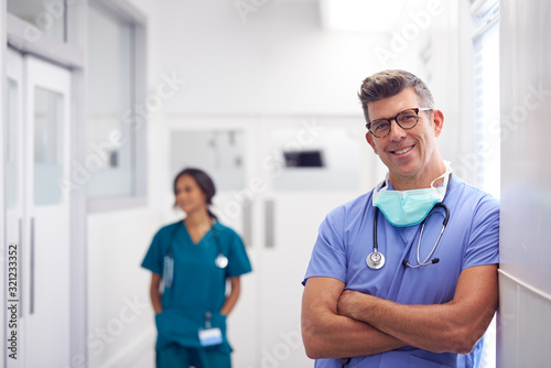 Photo Portrait Of Mature Male Doctor Wearing Scrubs Standing In Busy Hospital Corridor