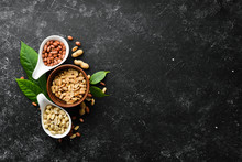 Set Of Peanuts In Bowls On A Black Stone Background. Nut Background. Top View.